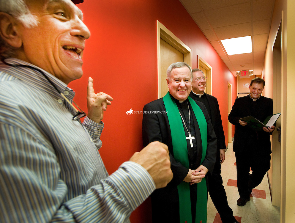 Martie Aboussie, executive director of Father Dempsey's Charities, shared a light- hearted moment with Archbishop Robert J. Carlson. The archbishop was at the facility to bless a new wing of building where eight new studio apartments were built.  Father Dempsey's Home has provided transitional housing since 1906. Also pictured are Vicar General Msgr. Vernon E. Gardin and Father Brian Fischer, the archbishop's secretary.