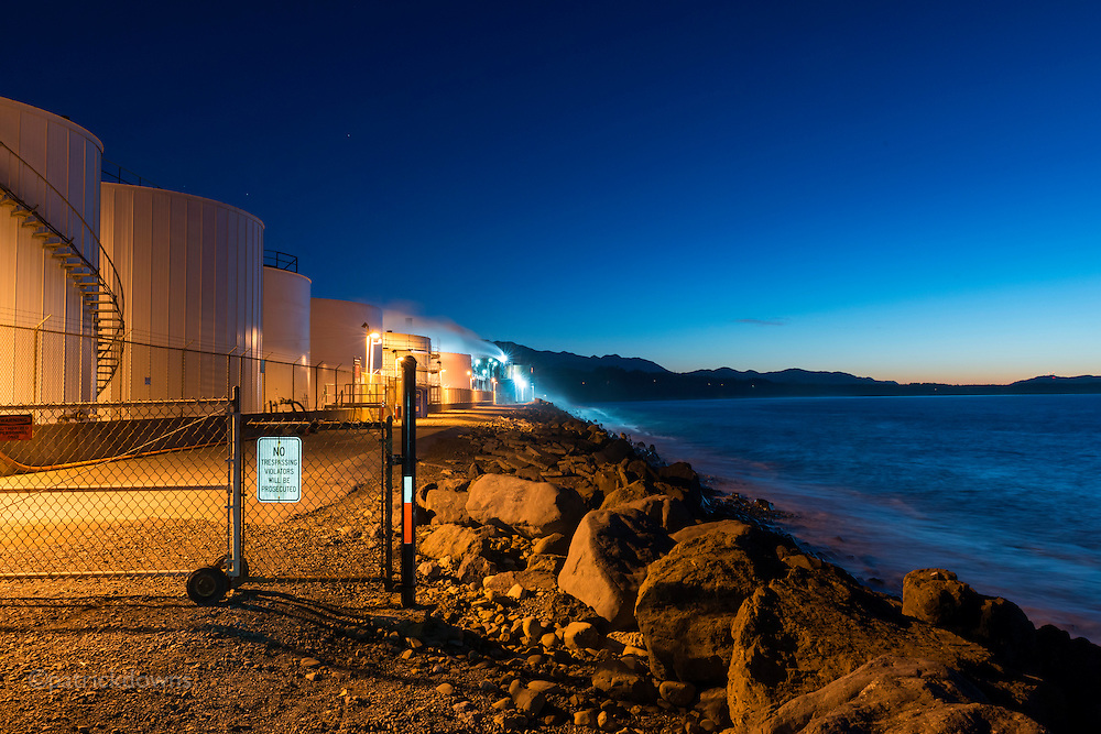 Industrial seascape: The Nippon paper plant glows at deep dusk, as waves wash on to the shore of the Strait of Juan de Fuca and Ediz Hook in Port Angeles.