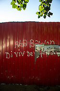 "Graffiti reading ""Down with the baron. Long live development,"" is seen on a construction fence, along with a picture of the replacement Ministry of Economy and Finance, stands where the former ministry, destroyed in the 2010 quake used to be, in Port-au-Prince, Haiti, January 4, 2015.  The building was deconstructed brick by brick by local residents who sold the materials to construction companies.  The lot behind the fence remains empty. The ""baron"" refers to President Michel Martelly, who will rule by decree if an agreement with parliament allowing elections does not happen by January 12, the five year anniversary of the quake."