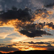 Sunset turns clouds orange in a blue sky over Idaho, USA.