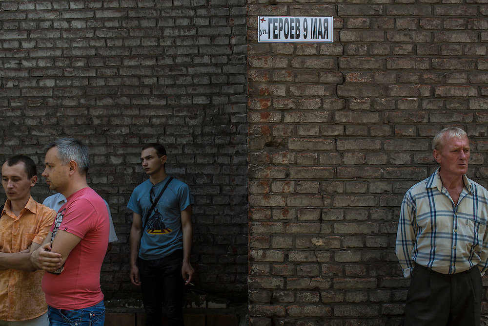 MARIUPOL, UKRAINE - MAY 18: People attend a memorial service at a police station which was earlier destroyed in a violent clash, resulting in seven deaths, on May 18, 2014 in Mariupol, Ukraine. A week before presidential elections are scheduled, questions remain whether the eastern regions of Donetsk and Luhansk are stable enough to administer the vote. (Photo by Brendan Hoffman/Getty Images) *** Local Caption ***