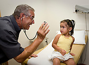 A volunteer physician tries to gain a young patient's trust at a free medical clinic.