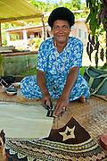 Fijian woman painting design on tapa cloth; Tongo village,  Qamea Island, Fiji.