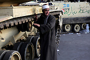 An Egyptian man weeps as he stands nearby military vehicles during clashes between anti and  pro-government protestors in Tahrir Square February 2,2011. (Photo by Heidi Levine/Sipa Press).
