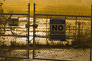 """A """"No Trespassing"""" sign on a foggy night in an urban setting."""