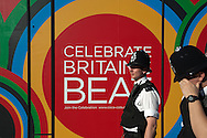 Policeman walks past an advertisement on the way to a technical rehearsal for the Olympic Opening Ceremony for the 2012 Olympic Games, at the Olympic stadium, London.