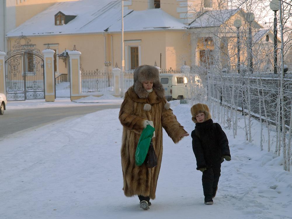 Mutter und Sohn in der Innenstadt von Jakutsk. Jakutsk wurde 1632 gegruendet und feierte 2007 sein 375 jaehriges Bestehen. Jakutsk ist im Winter eine der kaeltesten Grossstaedte weltweit mit durchschnittlichen Winter Temperaturen von -40.9 Grad Celsius. Die Stadt ist nicht weit entfernt von Oimjakon, dem Kaeltepol der bewohnten Gebiete der Erde.<br /> <br /> Mother and son in the city center of Yakutsk. Yakutsk was founded in 1632 and celebrated 2007 the 375th anniversary - billboard announcing the celebration. Yakutsk is a city in the Russian Far East, located about 4 degrees (450 km) below the Arctic Circle. It is the capital of the Sakha (Yakutia) Republic (formerly the Yakut Autonomous Soviet Socialist Republic), Russia and a major port on the Lena River. Yakutsk is one of the coldest cities on earth, with winter temperatures averaging -40.9 degrees Celsius.