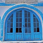 Thirasia Island (or Therasia), Santorini, Greece: arched cyan blue door with glass windows.