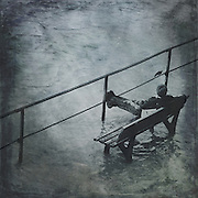 Boy sitting on a bench amidst a flooded promenade.