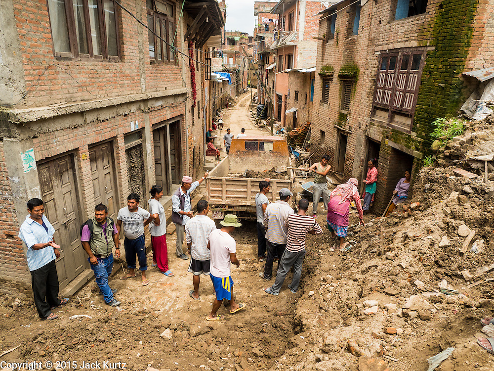 04 AUGUST 2015 - KHOKANA, NEPAL: Workers remove earthquake debris from the streets in Khokana, a village about an hour from Kathmandu. Three months after the earthquake, roads in many rural villages are still blocked by earthquake debris. The Nepal Earthquake on April 25, 2015, (also known as the Gorkha earthquake) killed more than 9,000 people and injured more than 23,000. It had a magnitude of 7.8. The epicenter was east of the district of Lamjung, and its hypocenter was at a depth of approximately 15 km (9.3 mi). It was the worst natural disaster to strike Nepal since the 1934 Nepal–Bihar earthquake. The earthquake triggered an avalanche on Mount Everest, killing at least 19. The earthquake also set off an avalanche in the Langtang valley, where 250 people were reported missing. Hundreds of thousands of people were made homeless with entire villages flattened across many districts of the country. Centuries-old buildings were destroyed at UNESCO World Heritage sites in the Kathmandu Valley, including some at the Kathmandu Durbar Square, the Patan Durbar Squar, the Bhaktapur Durbar Square, the Changu Narayan Temple and the Swayambhunath Stupa. Geophysicists and other experts had warned for decades that Nepal was vulnerable to a deadly earthquake, particularly because of its geology, urbanization, and architecture.     PHOTO BY JACK KURTZ