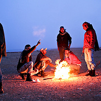 Rebel fighters cook meat over a fire near the front line on the outskirts of Ras Lanuf, Libya. March 2011.