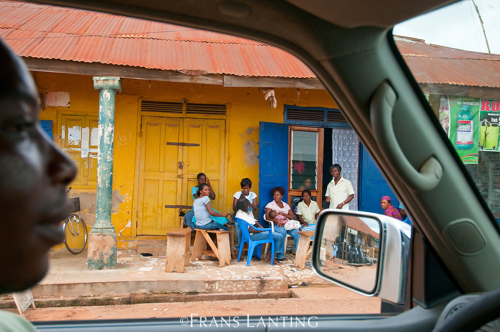 Driver passing people gathered on front porch, Ghana