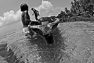 """Isla Grande is an exciting and popular place in Panama that people simply know as """"La Isla"""" (The Island). The island is inside the Portobelo National park, just 5 minutos by motor boat from the small town of La Guaira on the main land that makes its living out fishing and tourism.Pictured: Local Panamenian children fishingPictured: Garbage floating on the ocean"""