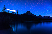 A long exposure image of the night sky over Waterfowl Lakes on the Icefields Parkway in Banff National Park. It was extremely dark and many more stars than we can normally see were visible in the sky. The trees and mountains reflecting in the water were an added bonus.<br /> <br /> &copy;2015, Sean Phillips<br /> http://www.RiverwoodPhotography.com