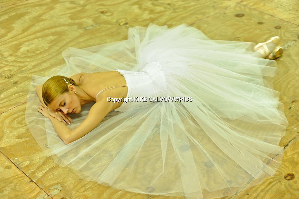 MR. Model relased photo. Cuban ballerina sleeps on the wooden floor wearing a romantic dress.
