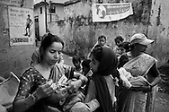 Administering the polio vaccination outside the Madrassa Abdul Salam in Pakbara town, Taspur Block, Moradabad. The clinic was inaugurated by Shamme Alam Shahar Imam (not photographed). <br /> <br /> In September 2006, Pakbara town in Taspur Block achieved 86 percent polio vaccination coverage. For the November 12th BMCs (Block Mobilisation Coordinators) and CMCs (Community Mobilisation Coordinators) were aiming for above 90percent. With poor sanitation and overcrowded living conditions, Pakbara town is considered a high risk polio infection area. The population of Pakbara town is 40-50,000. In Taspur block there are four BMCs. Together they have informally labeled the November 12th round &quot;Mission New Born&quot;. The next round will be &quot;Mission X-R&quot; with a focus on families refusing to have their children vaccinated. <br /> <br /> Photo: Tom Pietrasik<br /> Moradabad, Uttar Pradesh, India.<br /> November 12th 2006