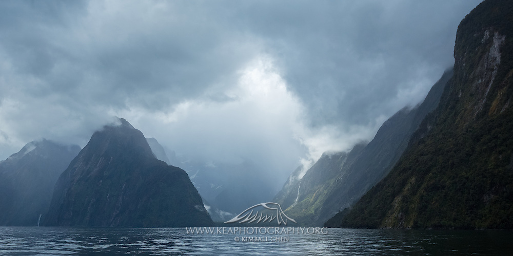 In the midst of a storm, a beam of sunlight breaks through and graces the remnants of the Pembroke glacial valley in Milford Sound, Fiordland National Park
