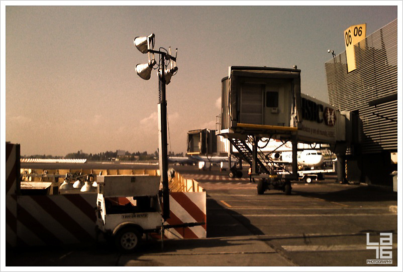 still life at T2 Mexico Benito Juarez airport. plane dock, lights, food cart, bag cart, 06, lane.