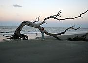 Red head woman walking Driftwood Beach at sunset