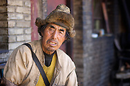 A gruff Tibetan man wearing a fur hat looks at the camera in Dequin, China.