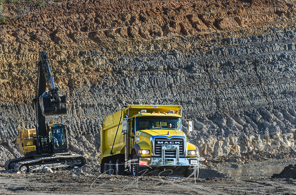 An employee with KR Trucking loads kaolin clay into a 2015 Mack Granite dump truck, Sept. 20, 2016, in Huntingdon, Tenn. The company, which mines both kaolin and ball clay, uses primarily Mack Granites in its fleet. (Photo by Carmen K. Sisson/Cloudybright)