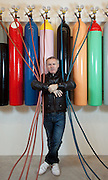 "Damien Hirst portrait with his artwork.""Greetings from the Gutter/ Avoiding the Inevitable"".1994.Glass, steel, gas cylinders, rubber, acrylic, MDF, gas mask, saline bags and needle.Dimensions variable.© Damien Hirst. All rights reserved, DACS 2010.Photographed in his Chalford Studio, near Stroud, Gloucestershire"