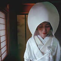 "Wedding day for Tazuko Kojima of Kyoto Japan.  Here, she wears a traditional head covering to hide ""horns of jealousy. The wedding is the central event in the life of a Japanese woman."