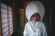 """Wedding day for Tazuko Kojima of Kyoto Japan.  Here, she wears a traditional head covering to hide """"horns of jealousy. The wedding is the central event in the life of a Japanese woman."""