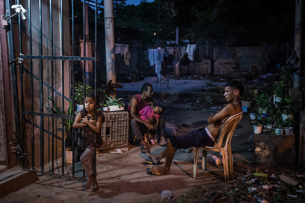 """CUMANÁ, VENEZUELA - JUNE 16, 2016: The Reina-Rodríguez family sits outside of their home, hungry because they had to skip dinner because they could not find any food that they could afford, despite searching different stores for hours.  The only food they had in their home were two limes and several jugs of water, stored in their refridgerator.  The family had eaten bread for breakfast and soup made from fish that Mr. Reina had managed to catch. """"We rarely are able to eat three meals a day,"""" Mrs. Rodríguez said. PHOTO: Meridith Kohut for The New York Times"""