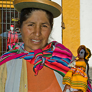 "Woman offering her handmade dolls in the ""White City"" of Arequipa, Peru."