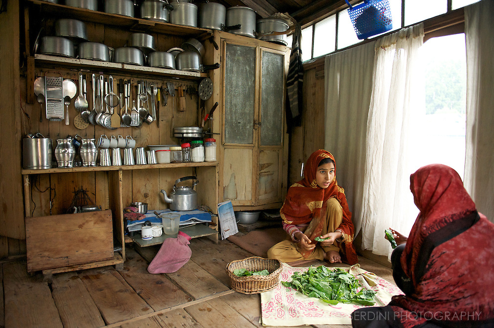 Women clean greens in a kitchen. No chairs or beds are used on houseboats. Local dwellers sits and sleep on the floor. Dal Lake. Srinagar. Kashmir. India