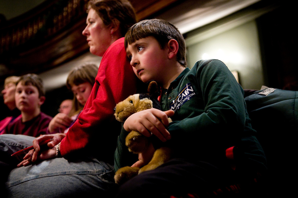 A boy listens as Sen. John McCain (R-AZ) speaks at a presidential campaign rally in Newport, NH, on Sunday, Dec. 30, 2007.