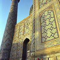 Visitors at dusk to the Sher Dor Medressa, once an important Islamic studies teaching school, now a tourist attraction, Registan Square, Samarkand, Uzbekistan.