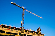 A tall heavy duty tower crane stands high above a new condominium high rise project on the south side of Chicago, IL.