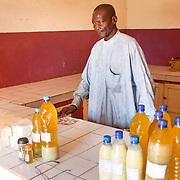 LÉGENDE: Le responsable de vente des produits fabriqués dans le centre tels que le beurre de Karité et d'autres variétés. LIEU: Centre COFEMAK, Koumra, Tchad. PERSONNE(S): Responsable de vente (au milieu).
