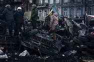 Sitting on pile of tires and charred police bus, anti government protester stands<br />  guard on Hrushevskoho street barricades near Maidan Square during standoff with riot police while a truce was agreed, in Kiev, 27 January 2014.