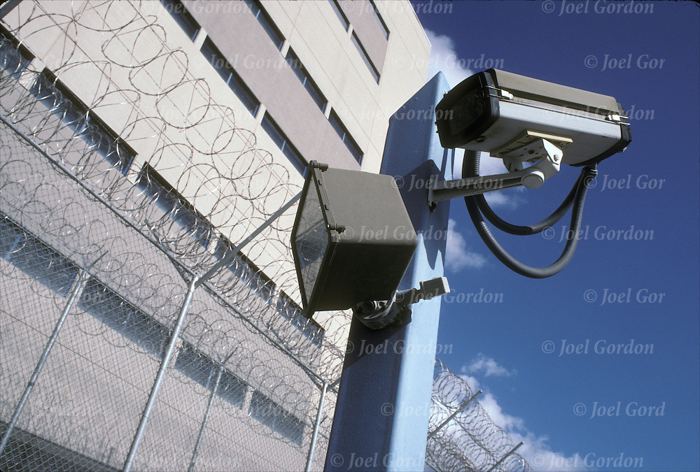 Security camera and razor wire on perimeter fence of jail