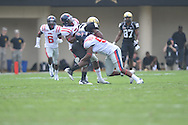 Vanderbilt running back Wesley Tate (24) is tackled by Ole Miss' Aaron Garbutt (20) and Ole Miss' Mike Marry (52) in Nashville, Tenn. on Saturday, September 17, 2011. Vanderbilt won 30-7..