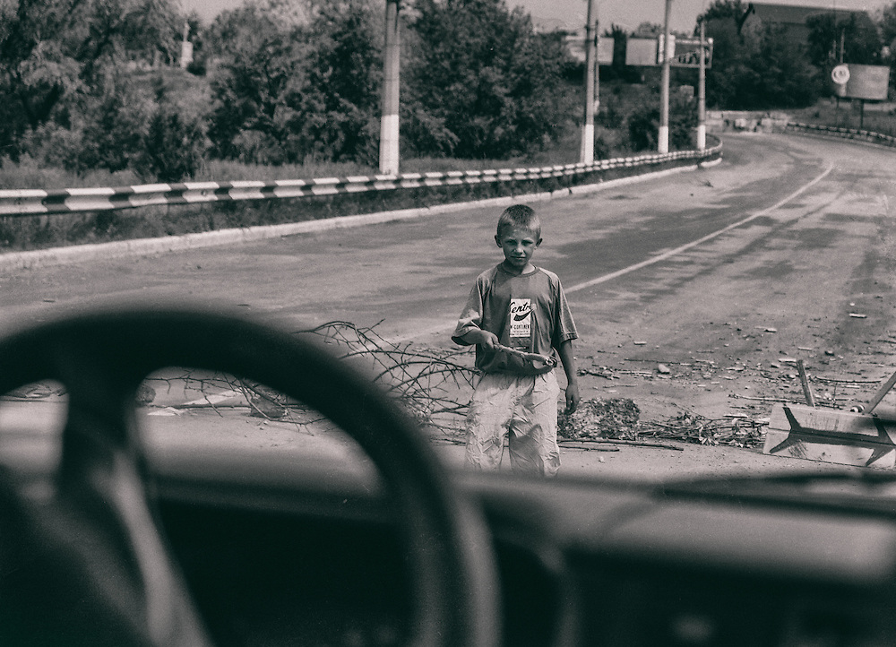 14 May 2014 - Ukraine - Slaviansk -  This photo explain well the chaotic and sometime ridiculous of the situation in east of Ukraine. A kid, probably around 8 years old make his own barricade with tree's branches and act like he's an official forcing car to detour. Nobody want to crash a kid, so car obey.