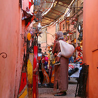 North Africa, Africa, Morocco, Marrakesh.  A Morrocan woman shops for lamps with a baby slung on her back in the souks of Marrakesh.