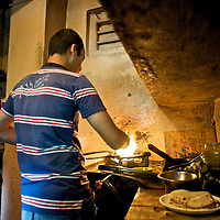 A man cooks Indian bread on a stove in the kitchen of a small restaurant in the village of Giabong in the Ropa Valley of Himachal Pradesh, India