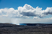 "Halema'uma'u Crater is an active pit crater containing a steaming lava lake, within the much larger summit caldera of Kilauea in Hawaii Volcanoes National Park on the Big Island, Hawaii, USA. With its name meaning ""house of the 'ama'u fern,"" Halemaumau is home to Pele, goddess of fire and volcanoes according to Hawaiian mythology. Established in 1916 and later expanded, the park (HVNP) encompasses two active volcanoes: Kilauea, one of the world's most active volcanoes, and Mauna Loa, the world's most massive shield volcano. The park portrays the birth of the Hawaiian Islands with dramatic volcanic landscapes, native flora and fauna, and glowing flowing lava. HVNP is honored as a UNESCO World Heritage Site and International Biosphere Reserve."