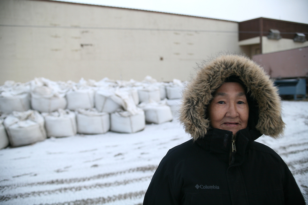 A lady standing in front of sand bags that enforce the sea wall in Kivalina, Alaska. 2009
