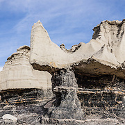 Eroded badlands of Bisti/De-Na-Zin Wilderness, south of Farmington, in San Juan County, New Mexico, USA. This fantasy world of strange rock formations is made of interbedded sandstone, shale, mudstone, coal, and silt. These rock layers have weathered into eerie hoodoos (pinnacles, spires, and cap rocks). This was once a riverine delta west of an ancient sea, the Western Interior Seaway, which covered much of New Mexico 70 million years ago. Swamps built up organic material which became beds of lignite. Water disappeared and left behind a 1400-foot (430 m) layer of jumbled sandstone, mudstone, shale, and coal. The ancient sedimentary deposits were uplifted with the rest of the Colorado Plateau, starting about 25 million years ago. Waters of the last ice age eroded the hoodoos now visible. The high desert widerness of Bisti is managed by the US Bureau of Land Management (BLM). This panorama was stitched from 3 overlapping photos.