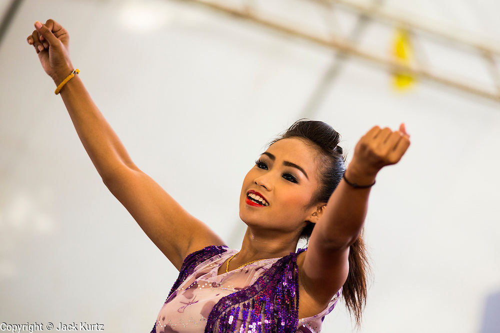 """15 JUNE 2014 - BANGKOK, THAILAND: A dancer performs during a """"Return Happiness to Thais"""" party in Lumpini Park in Bangkok. The Thai military junta, formally called the National Council for Peace and Order (NCPO), is sponsoring a series of events throughout Thailand to restore """"Happiness to Thais."""" The events feature live music, dancing girls, military and police choirs, health screenings and free food.   PHOTO BY JACK KURTZ"""