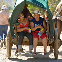 Two women eat snacks while riding on the back of an Ox cart.Ox carts have ben used in Guanacaste for hundreds of years. Although few are still built, all are used on a daily basis