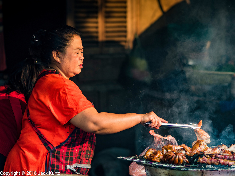 """13 MARCH 2016 - LUANG PRABANG, LAOS: A woman grills meat in the market in Luang Prabang. Luang Prabang was named a UNESCO World Heritage Site in 1995. The move saved the city's colonial architecture but the explosion of mass tourism has taken a toll on the city's soul. According to one recent study, a small plot of land that sold for $8,000 three years ago now goes for $120,000. Many longtime residents are selling their homes and moving to small developments around the city. The old homes are then converted to guesthouses, restaurants and spas. The city is famous for the morning """"tak bat,"""" or monks' morning alms rounds. Every morning hundreds of Buddhist monks come out before dawn and walk in a silent procession through the city accepting alms from residents. Now, most of the people presenting alms to the monks are tourists, since so many Lao people have moved outside of the city center. About 50,000 people are thought to live in the Luang Prabang area, the city received more than 530,000 tourists in 2014.    PHOTO BY JACK KURTZ"""