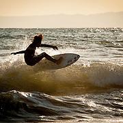 A surfer catches a wave at Shonan Beach in Fujisawa, Kanagawa Prefecture, Japan.