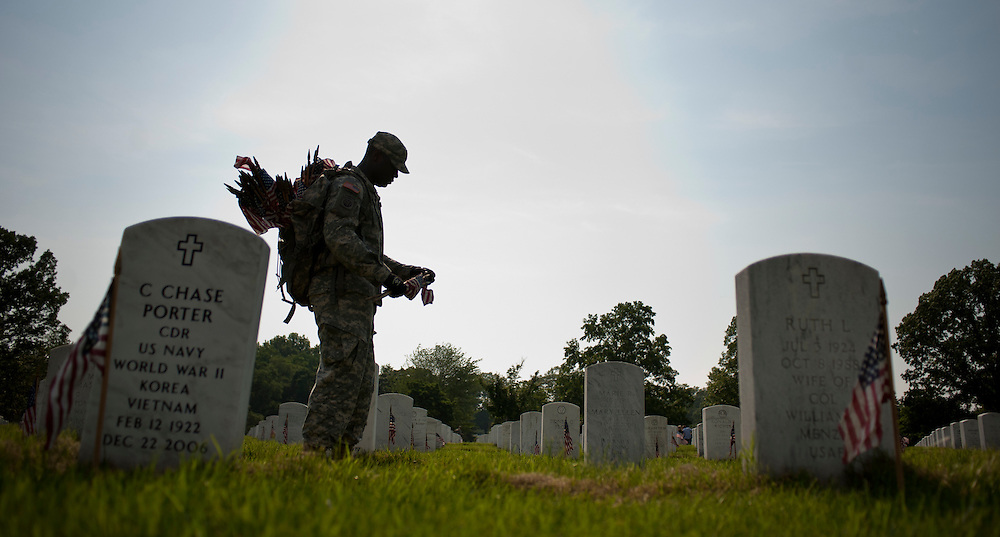 "Members of the 3rd U.S. Infantry, known as The Old Guard, place American flags before gravestones and niches of service members buried at Arlington National Cemetery in advance of the Memorial Day weekend. The tradition, known as ""flags in,"" is conducted annually since 1948. Every available soldier in the 3rd U.S. Infantry participates, placing small American flags one foot in front and centered before more than 260,000 gravestones and about 7,300 niches at the cemetery's columbarium. Old Guard soldiers remain in the cemetery throughout the weekend, ensuring that a flag remains at each gravestone."