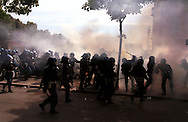 Police confront demonstrators with tear gas and batton charges outside the centre of Genoa, Italy. Banks, shops and cars were burnt and looted. The historic centre of the town had been sealed off for the G8 Summit. Up to 40 % of the city's population left the city and 15,000 police and army personnel sealed off the historic centre in anticipation of violent demonstrations. Up to 100,000 demonstrators protested against global capitalism and world poverty during the summit. .